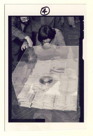 """Caja de acrílico en la Galería Centro Imagen. Santiago de Chile (1979). En la foto: Juan Castillo terminando de pegar la tapa de la caja. Acción""""Para no morir de hambre en el arte"""". CADA // Archivo en uso."""
